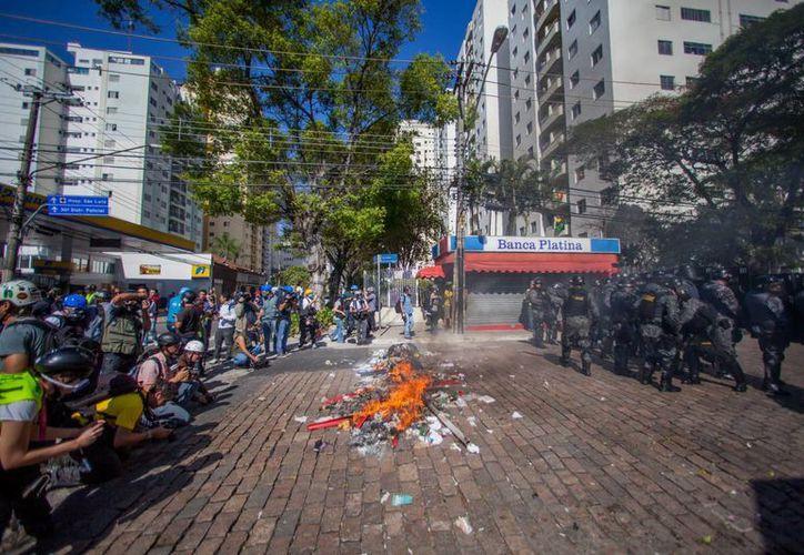 Miembros de la Policía brasileña dispersan a un grupo de manifestantes en Sao Paulo durante una protesta contra el Mundial de fútbol. (EFE)