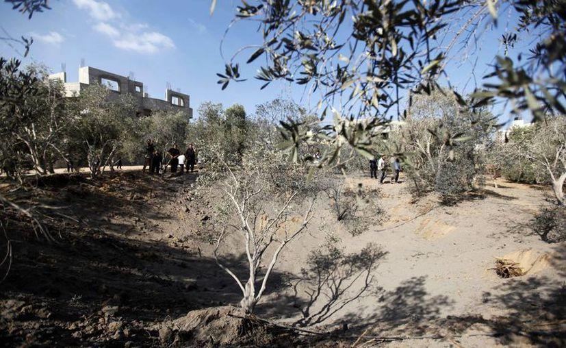 Soldados de Hamas revisan la zona donde se registró un bombardeo. (Agencias)