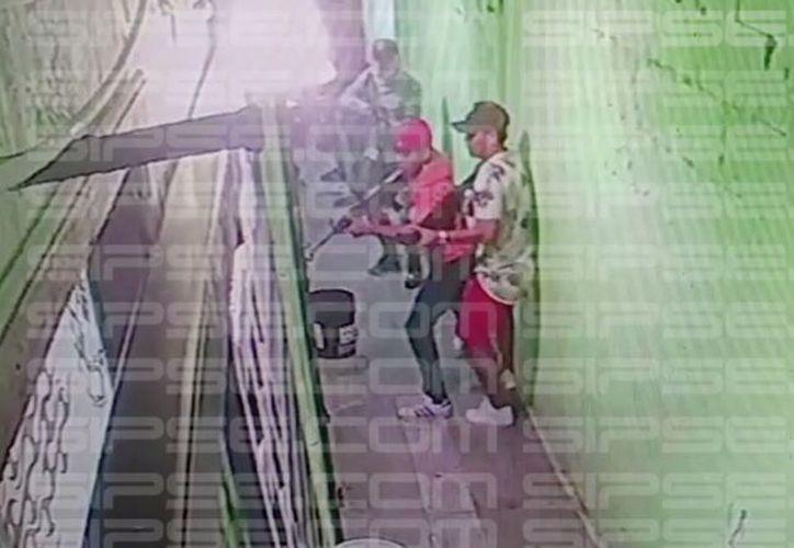El taxista escapa, mientras que es seguido por al menos cinco sujetos armados que aparecen en los videos. (Captura de pantalla)
