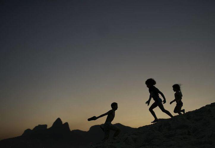 Google dio a conocer su plataforma de transmisión de los Juegos Olímpicos. En la foto, de contexto, niños juegan en la playa brasileña de Ipanema. (AP)