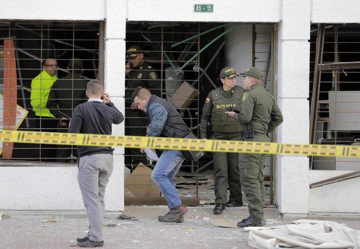 Policías inspeccionan el lugar donde explotó uno de los artefactos en la zona bancaria de Bogotá, Colombia, el 2 de julio de 23015. (Foto AP)