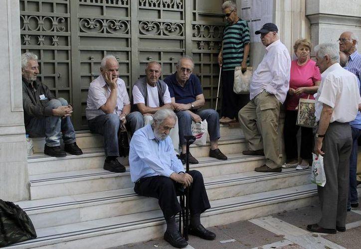 Pensionistas que no poseen tarjeta de crédito esperan para cobrar a las afueras de una sucursal del Banco Nacional de Grecia en Atenas, Grecia, hoy. (EFE)