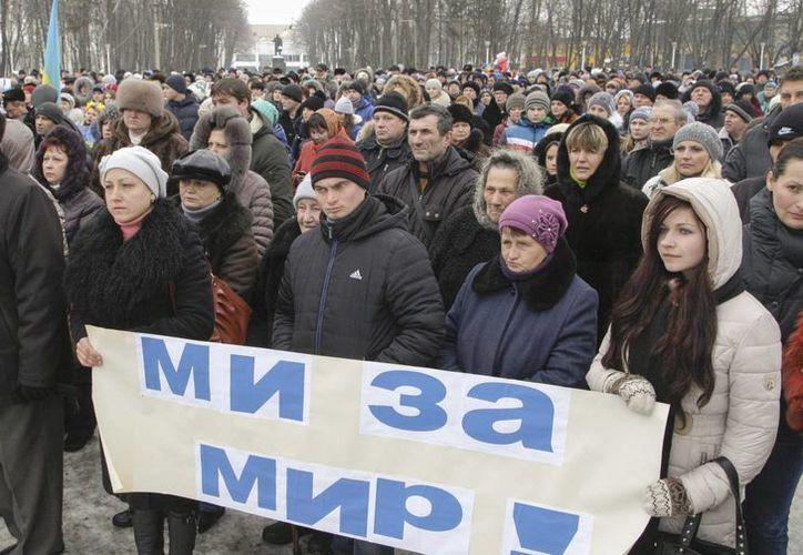 Varias personas partipantes en una marcha en Kiev sostienen una pancarta en la que puede leerse 'Queremos paz'. (EFE)