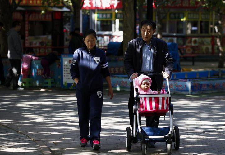 La decisión de abolir la política de un hijo es un beneficio inesperado para las empresas que venden desde leche para infantes hasta pañales y juguetes. En la imagen, un abuelo pasea con su nieto y su hija por un parque de Beijing, China. (EFE)