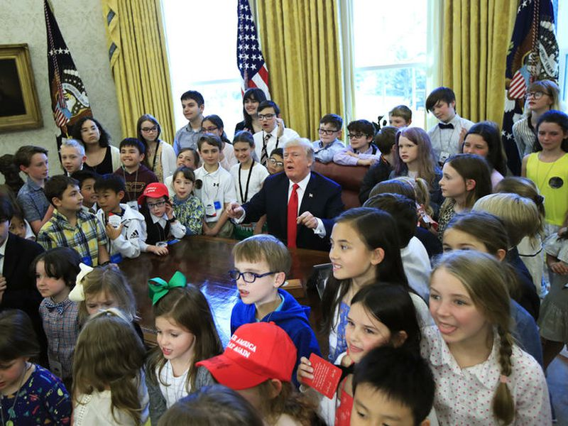 """President Donald Trump is surrounded by children kids in the Oval Office in celebration of """"Bring Our Daughters and Sons to Work Day"""" at the White House in Washington."""