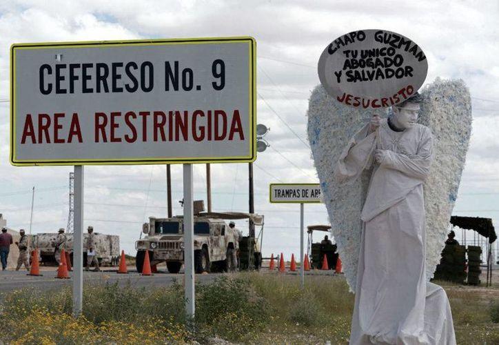 Un miembro de la organización evangélica 'Los Ángeles Mensajeros' sostiene un cartel frente a la entrada a la prisión donde es retenido el capo del narcotráfico Joaquín 'El Chapo' Guzmán en Ciudad Juárez, México, el sábado 24 de septiembre de 2016. (AP Foto/Christian Torres)