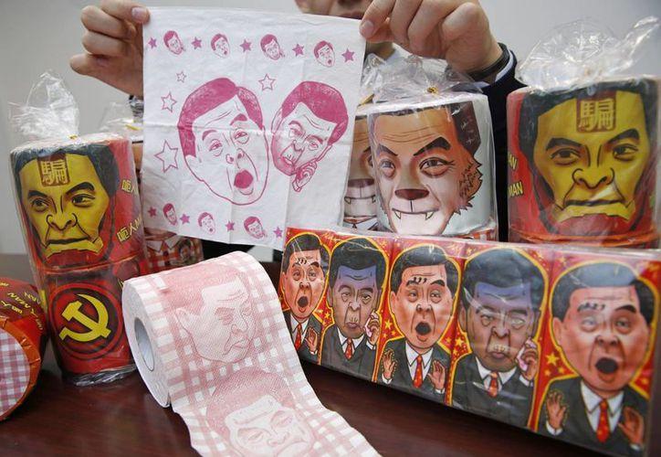 Rollos de papel higiénico y paquetes de pañuelos de papel con imágenes del líder hongkonés próximo a Beijing Leung Chun-ying, mostrados por el vicepresidente del Partido Democrático de Hong Kong Lo Kin-hei. (Agencias)
