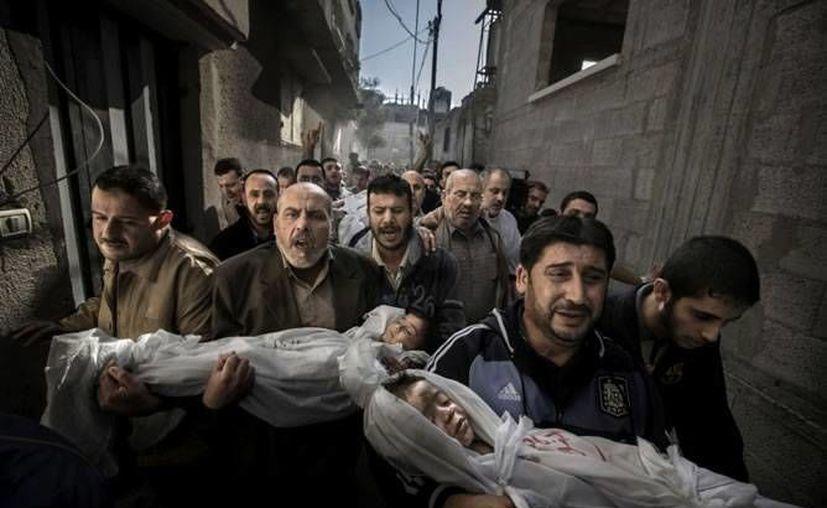 La fotografía muestra a un grupo de hombres que lleva el cuerpo de dos niños muertos. (cadenaser.com/Archivo)