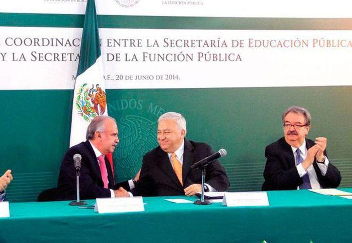 Julián Olivas (izq) y Emilio Chuayffet 'señan' simbólicamente, con un salud de manos, el acuerdo para la creación de la Universidad Abierta y a Distancia de México. (sep.gob.mx)