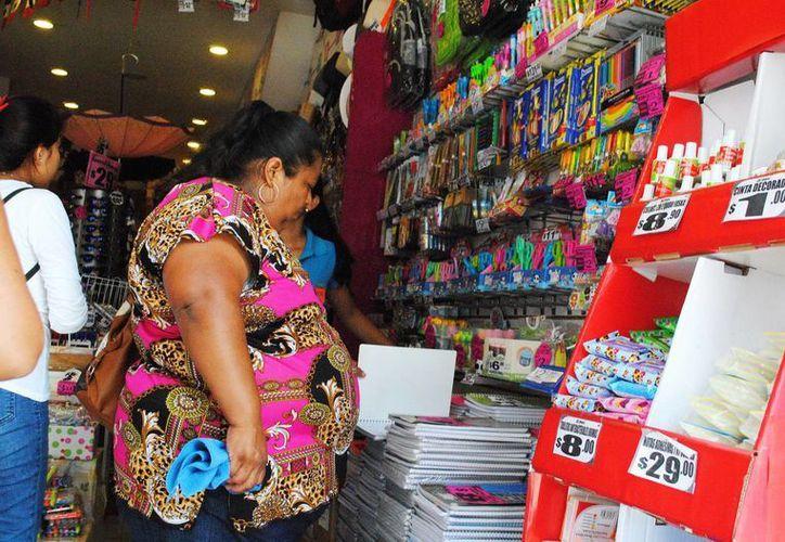 Empieza la venta fuerte en librerias y papelerías de la ciudad debido al regreso a clases. Imagen de una mujer mientras checa precios en una papelería. (Milenio Novedades)