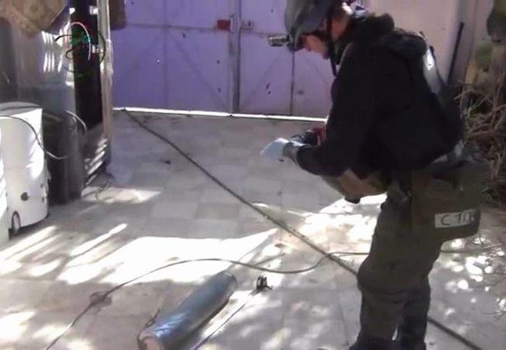En esta imagen tomada de un video amateur publicado en internet, un presunto miembro del equipo de investigación de la ONU mide y fotografía una lata en el suburbio de Moadamiyeh en Damasco, Siria. (Agencias)