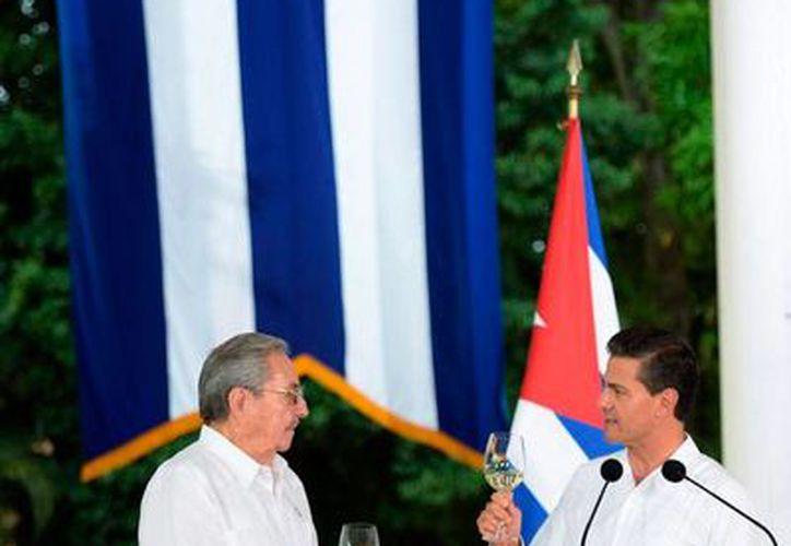 El presidente de Cuba, Raúl Castro (izq.), y el de México, Enrique Peña Nieto, brindaron por el bienestar del pueblo cubano, durante una comida en la Quinta Montes Molina, de Mérida. (presidencia.gob.mx)