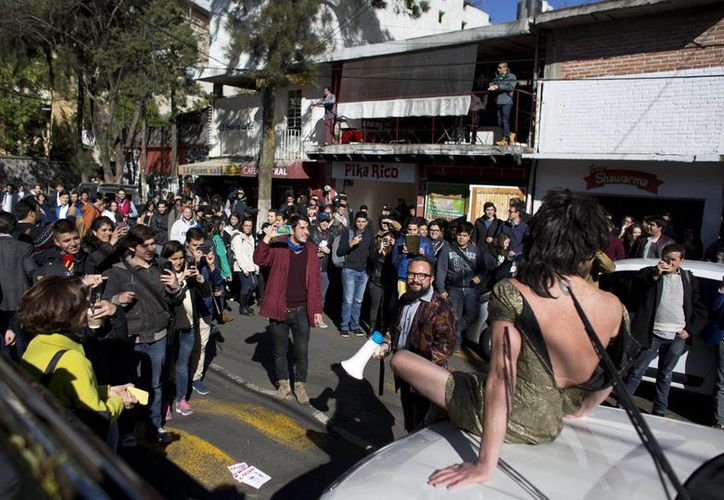 estudiantes observan a Arturo Hernández, sentado sobre un auto con un vestido, y a Alex Marin y Kall, con un megáfono, mientras ambos simulan ser una modelo y un vendedor que ofrece un auto mal estacionado. (Agencias)