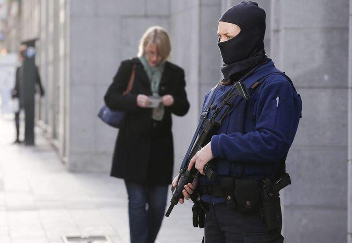Una agente de la policía belga armada vigila un edificio de la Policía Federal en Bruselas, Bélgica. (EFE/Archivo)