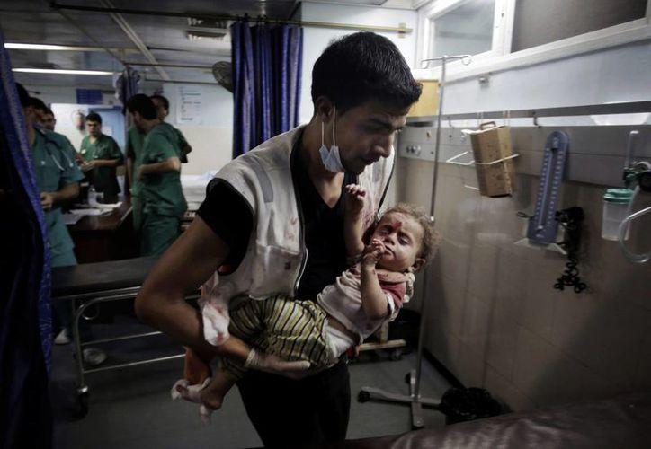 Un médico palestino carga a una niña herida en el hospital Shifa, en Gaza, el viernes 18 de julio de 2014.(Foto AP/Khalil Hamra)