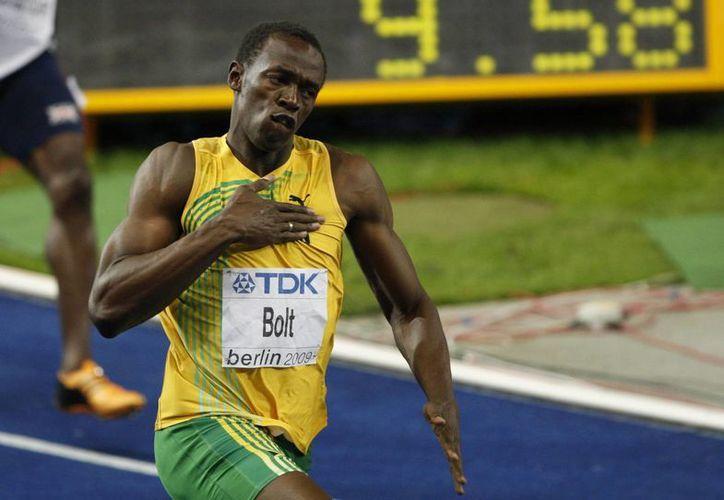 Usain Bolt y el estadio Nido de Pájaro comparten historias similares de éxito, en la foto Bolt durante el mundial de Atletismo celebrado en Berlín en 2009. (Archivo AP)
