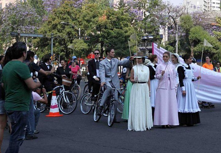 """Mozos, meseras, caballeros y damas de la alta sociedad, con sombreros y bicicletas antiguas, recorrieron esta mañana el Paseo de la Reforma, como parte de la promoción por el estreno de la telenovela """"El hotel de los secretos"""". (Notimex)"""