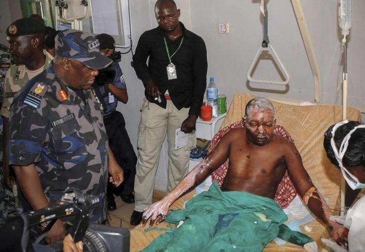 El jefe del Estado Mayor de la Defensa de Nigeria, Alex Badeh (i), visita a uno de los heridos en el atentado ocurrido en un mercado de la ciudad de Jos, Nigeria. (EFE)