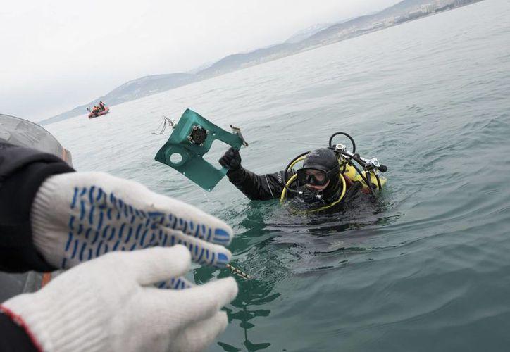 Un buzo del Ministerio de Emergencias de Rusia saca del mar un fragmento de un avión estrellado en el Mar Negro, en las afueras de Sochi. (AP/Viktor Klyushin)