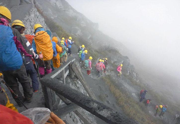 Montañistas se aprestan a abandonar el monte Ontake, en medio de la erupción. (Fotos: AP)
