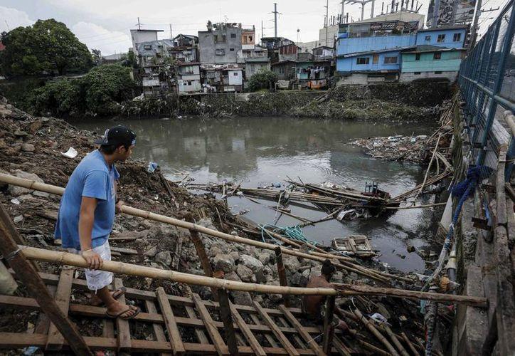 Dos hombres reparan un puente en Quezon al noreste de Manila, Filipinas. (EFE)