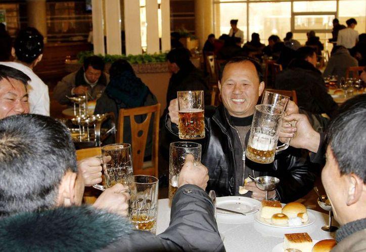 Norcoreanos brindan después de conocer la noticia del lanzamiento del cohete. (Agencias)