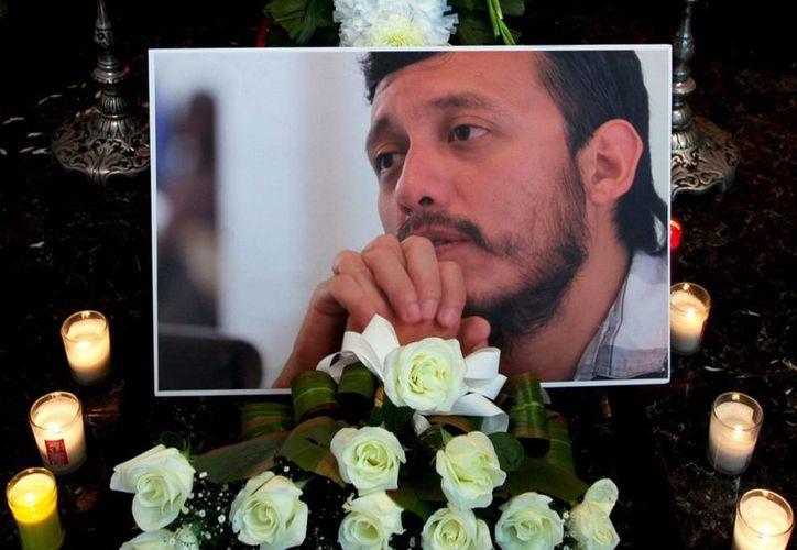 Una foto del asesinado fotoperiodista Rubén Espinosa fue colocada entre flores y velas en su ataud en una funeraria en ciudad de México este lunes 3 de agosto de 2015. (AP Photo/Marco Ugarte)