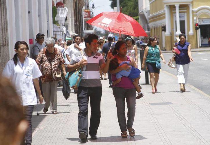 En Yucatán se pronostican temperaturas máximas de 34 a 38 grados centígrado. Imagen de una familia con sombrilla cerca de la Plaza Grande del centro de Mérida. (César González/SIPSE)