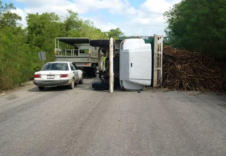 Un camión que trasladaba caña volcó en en el tramo Sabidos-Álvaro Obregón, la mañana del lunes. (Carlos Castillo/SIPSE)