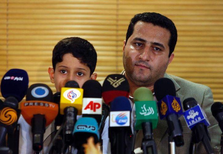 Foto del científico nuclear iraní Shahram Amiri, durante una conferencia de prensa, en julio de 2010, mientras sostiene a su hijo Amir Hossein en el aeropuerto Imam Khomeini de Teherán, Irán, después de regresar de Estados Unidos. (AP Foto/Vahid Salemi, Archivo)