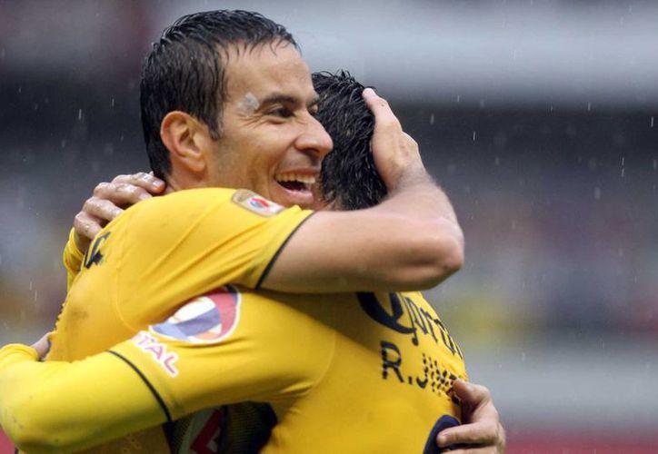 Luis Gabriel Rey felicita a Raúl Alonzo Jiménez, tras la tercera anotación del América, en partido contra Jaguares de Chiapas. (NTX)