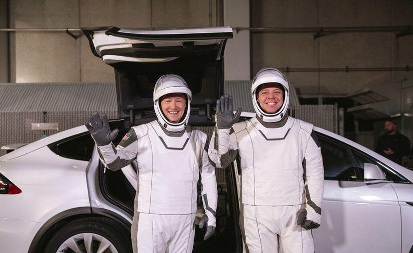 En esta fotografía del viernes 17 de enero de 2020 los astronautas Doug Hurley (izquierda) y Robert Behnken posan frente al automóvil eléctrico Model X de Tesla durante un ensayo de lanzamiento en el Centro Espacial Kennedy, en Cabo Cañaveral, Florida. (Kim Shiflett/NASA vía AP)