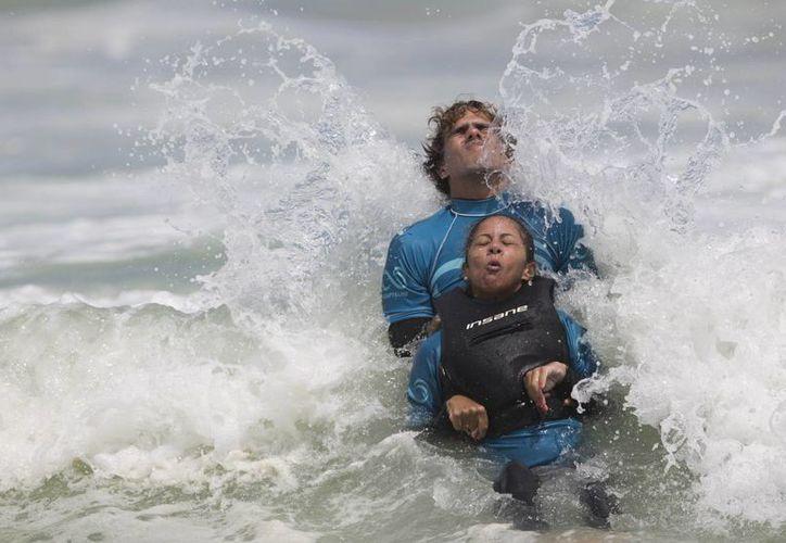 Ayudada por un voluntario de AdaptSurf, Monique Oliveira cabalga una ola en la playa de Barra de Tijuca, en Río de Janeiro. (Agencias)