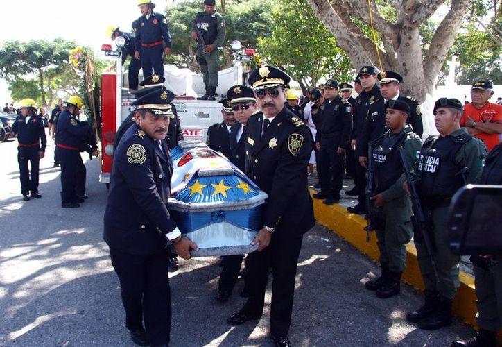 Luis Felipe Saidén Ojeda, Secretario de Seguridad Pública, y comandantes de la SSP, cargaron el féretro del primer inspector Manuel Fernando Solís Moguel. (Milenio Novedades)