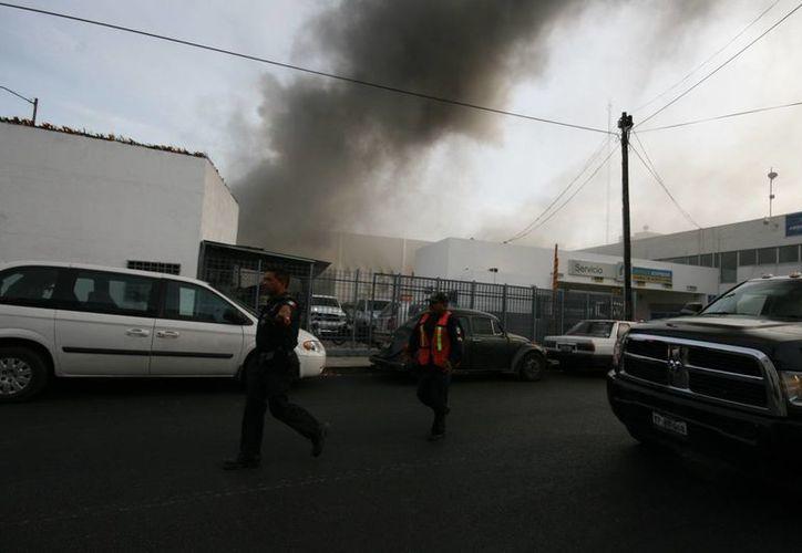 La policía y bomberos aseguraron los alrededores del lugar para evitar que el fuego en el taller de avenida Aviación se expandiera. (Jorge Sosa/SIPSE)