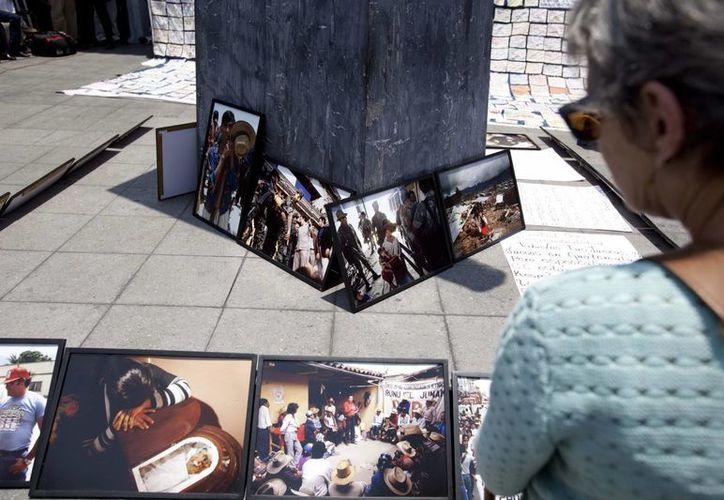 Una mujer observa las imágenes tomadas por la fotógrafa Jean Marie Simon realizadas durante la guerra interna de 36 años (1960-1996), colocadas frente a la Corte de Constitucionalidad. (EFE)