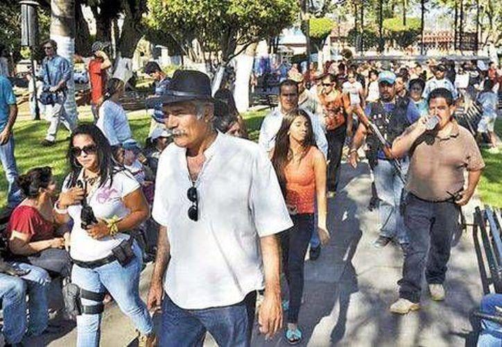 José Manuel Mireles encabezó la marcha y se dio tiempo de platicar con algunos participantes. (Milenio)