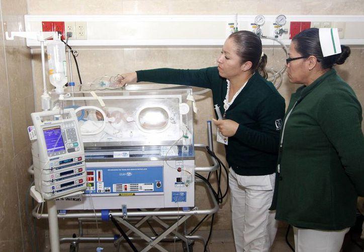 El rumor de la privatización de los servicios médicos del IMSS e Issste ha cobrado fuerza, aunque se ha desmentido. En la imagen, dos enfermeras laboran en el área de Pediatría del Hospital General Regional No.36 San Alejandro, del IMSS, de Puebla. (Archivo/Notimex)