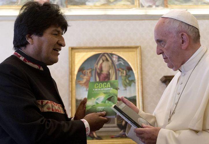 Imagen del momento en que Evo Morales le entrega al Papa Francisco los libros sobre los beneficios de la hoja de coca. (Agencias)