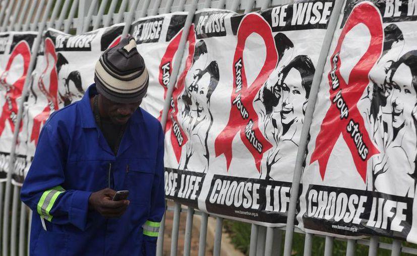 Un hombre pasa junto a unos cartolones colocados en relación al Día Mundial del SIDA en un edificio de oficinas en Sandton, Johannesburgo, Sudáfrica. (Agencias)