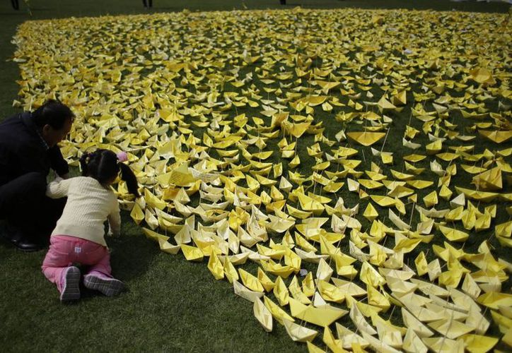 Una mujer coloca un barquito de papel junto a muchos otros a manera de tributo a las víctimas del hundimiento del ferry surcoreano Sewol. (Foto: AP)