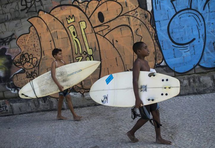 Wesley Mario (der) y Loran de Almeida, ambos de 13 años, caminan de regreso a la favela Rocinha tras surfear en la playa de Sao Conrado, en Río de Janeiro, Brasil. (Agencias)