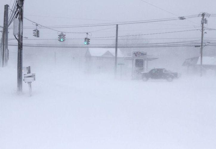 Una persona arriesga su vida al conducir un auto enmedio del frío congelante en Stafford, Nueva York. (Agencias)