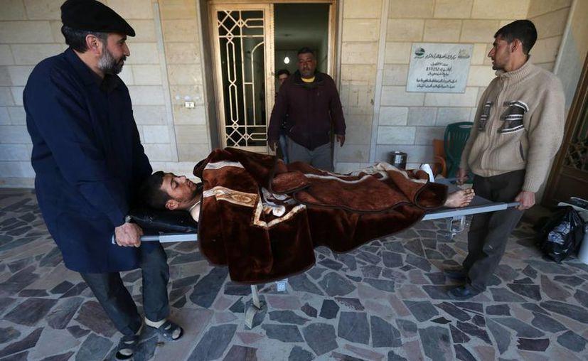 En la foto un enfermero libanés, izquierda, y un hombre sirio cargan en camilla a Adul-Karim, un rebelde sirio de 18 años que resultó herido durante una batalla contra soldados sirios y combatiente del Hezbolá en Rima, en Siria. (Agencias)