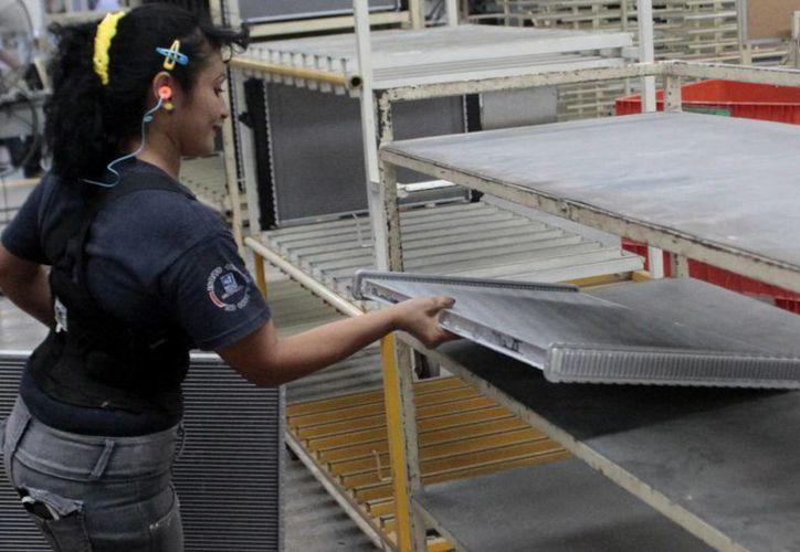 El 2015 fue un buen año para la industria manufacturera local. Fotografía de una trabajadora mientras labora en una empresa yucateca. (Milenio Novedades)