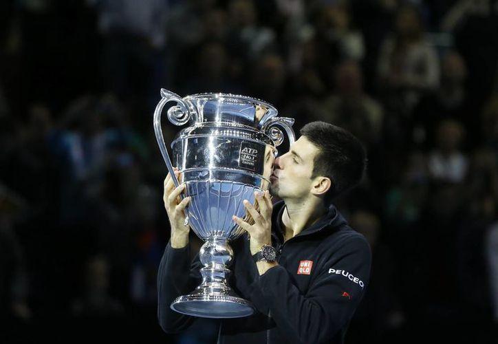 Djokovic besa el trofeo que lo acredita como el mejor tenista del mundo al terminar el 2014. (Foto: AP)