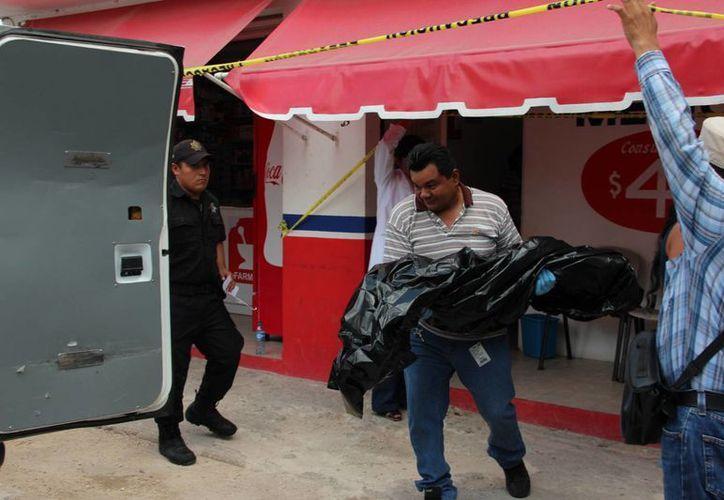 Momento en que es retirado el cuerpecito del menor del consultorio de la Farmacia Dr. Viera. (Foto: Aldo Pallota/SIPSE)