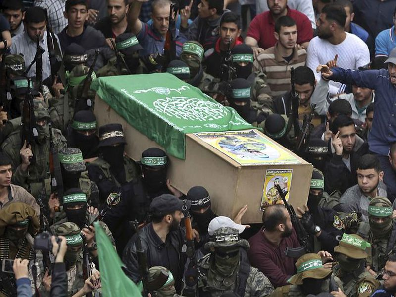 Masked Hamas gunmen carry the coffin of one of six of their fighters.
