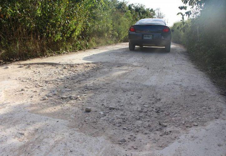 Delegados de la comunidad aseguran que el camino es prácticamente intransitable por los enormes baches que presenta.(Benjamín Pat/SIPSE)