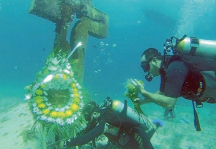 El buzo Alberto Friscione Carrasco y un grupo de amigos colocaron una ofrenda floral en la Cruz de la Bahía. (Foto: Luis Soto/SIPSE)